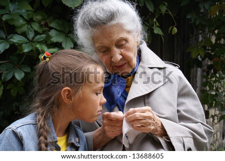 Granddaughter studying embroidery from her grandmother - stock photo