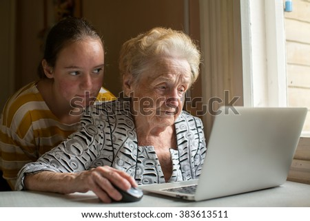 Granddaughter teaches her grandmother to type on the laptop. - stock photo