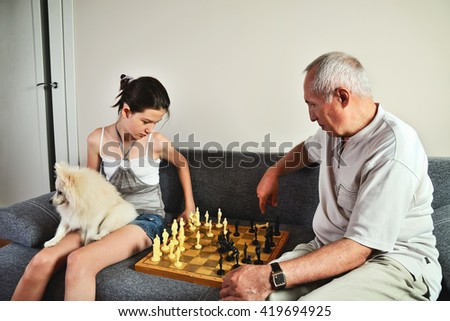 granddaughter with a dog and grandpa playing chess horizontal - stock photo