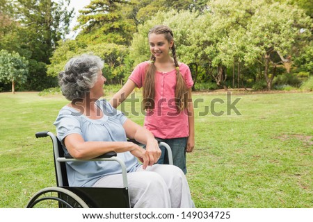 Granddaughter with grandmother in her wheelchair in the park  - stock photo