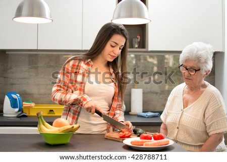 Granddaughter with grandmother preparing a salad in the kitchen. - stock photo