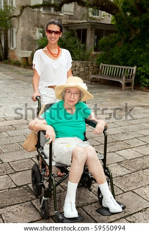 Granddaughter with handicapped senior grandmother in an outdoor garden setting.