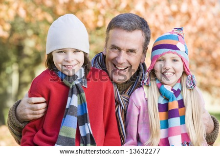 Grandfather and grandchildren on autumn walk - stock photo