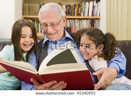 grandfather and grandchildren reading a book - stock photo