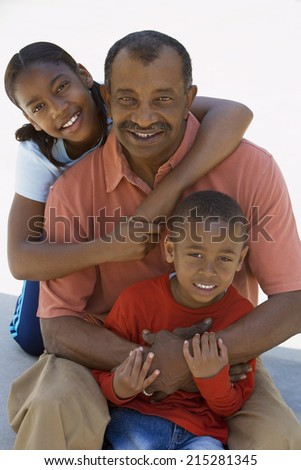 Grandfather and grandchildren (6-13) smiling, front view, portrait - stock photo