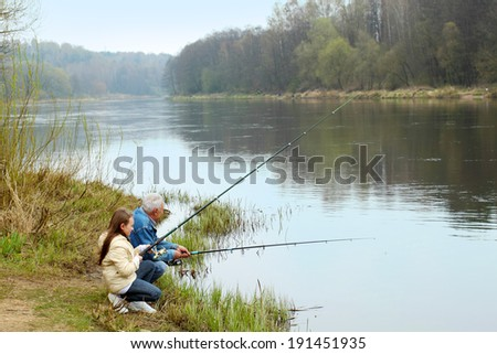 Grandfather and granddaughter are fishing - stock photo