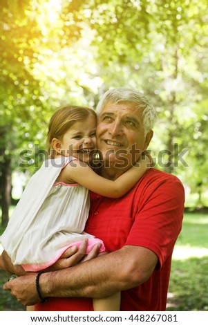 Grandfather and granddaughter enjoying in the park.