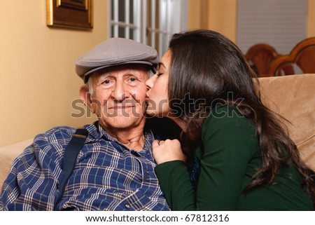 Grandfather and granddaughter in an affectionate lifestyle pose in a home setting.