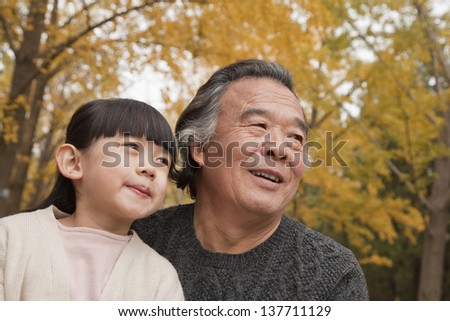 Grandfather and granddaughter in park - stock photo