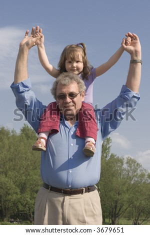 Grandfather and granddaughter looking at you over sky and trees background - stock photo