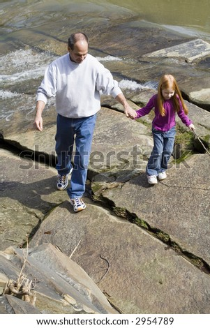 Grandfather and granddaughter on exploring a park. - stock photo