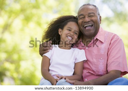 Grandfather and granddaughter outdoors smiling - stock photo