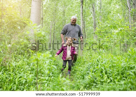 Grandfather and granddaughter running outdoor.