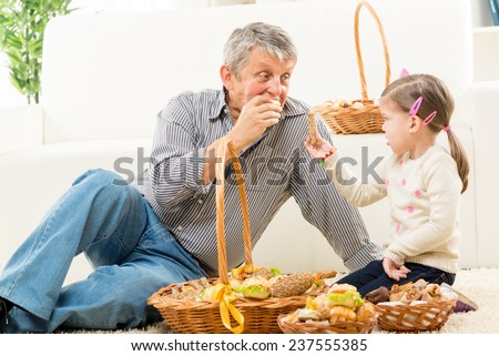 Grandfather and granddaughter sitting on a carpet in the living room next to woven baskets with pastries. They look at each other and eat pastry. - stock photo