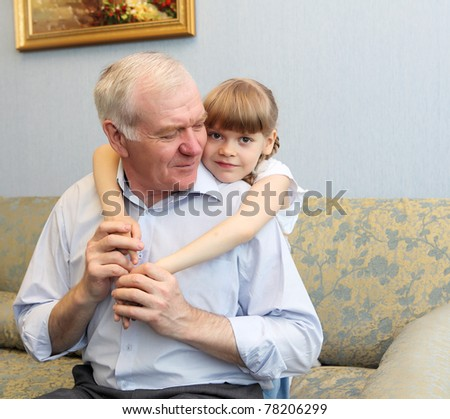 grandfather and granddaughter sitting on the sofa and hugging - stock photo