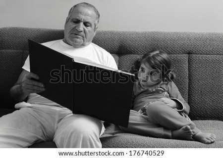 Grandfather and granddaughter sitting on the sofa and reading book before bedtime. - stock photo