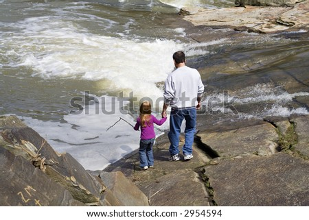 Grandfather and granddaughter standing at the river's edge. - stock photo