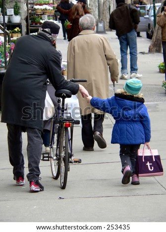 Grandfather and granddaughter walk after a bike ride.