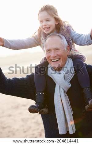 Grandfather And Granddaughter Walking On Winter Beach - stock photo