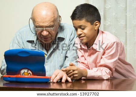 Grandfather and Grandson are seated at a table looking at a blue toy computer. Horizontally framed photograph. - stock photo