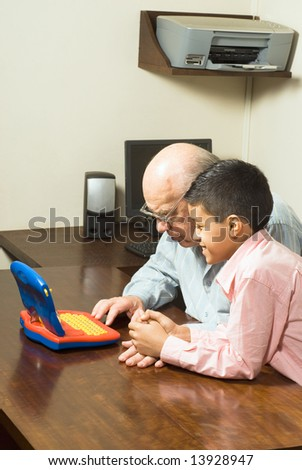 Grandfather and Grandson are seated at a table looking at a blue toy computer. There is a computer and a printer in the background. Vertically framed photograph. - stock photo