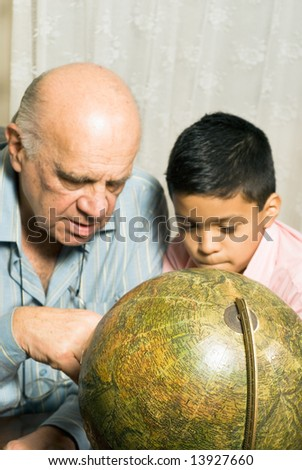 Grandfather and Grandson are seated at a table looking at a globe together. Vertically framed photograph. - stock photo
