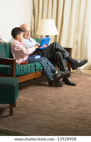 Grandfather and Grandson are seated on green couch looking at a blue laptop computer together. Vertically framed photograph. - stock photo
