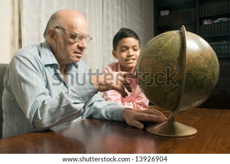 Grandfather and grandson are sitting at the table with a globe in front of them. Grandfather points to a location on the globe while grandson smiles beside him. This is a horizontally framed photo. - stock photo