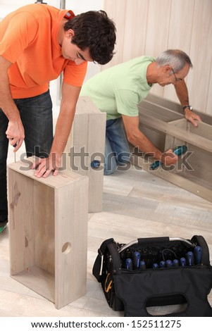 Grandfather and grandson assembling furniture