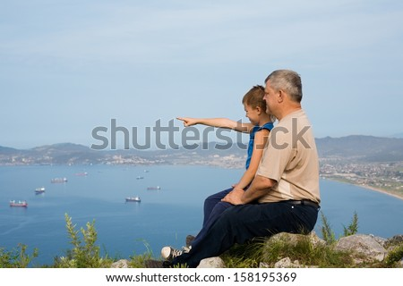 Grandfather and grandson at the top of the mountain. At the bottom of the sea and the city. - stock photo