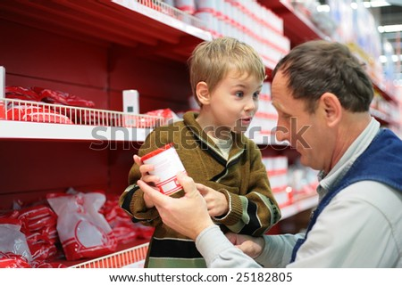 Grandfather and grandson choose conserve in food shop - stock photo