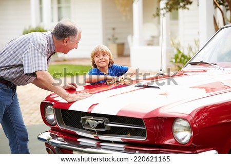 Grandfather And Grandson Cleaning Restored Classic Car - stock photo