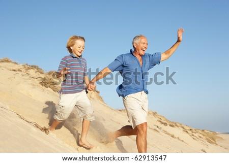 Grandfather And Grandson Enjoying Beach Holiday Running Down Dune - stock photo
