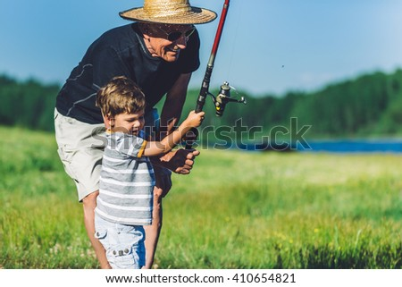 Grandfather and grandson fishing and having fun - stock photo