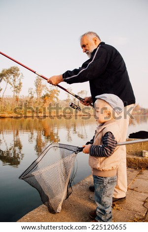 Grandfather and grandson fishing on the river. - stock photo