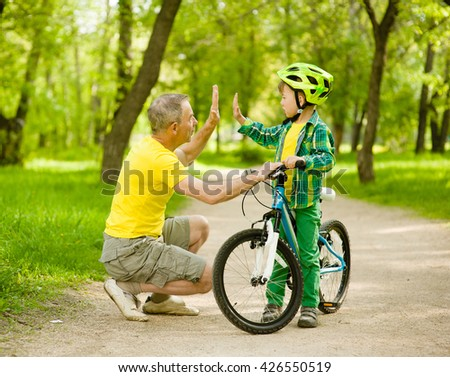 Grandfather and grandson give high five while cycling in the park. - stock photo