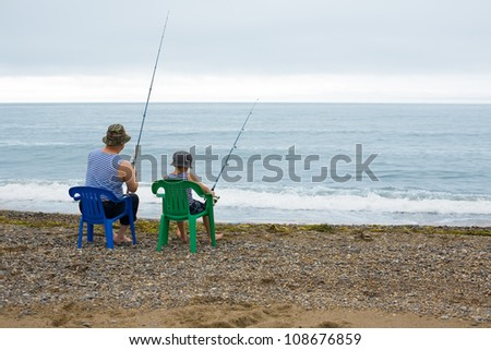 Grandfather and grandson go fishing in the sea. - stock photo