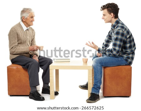 Grandfather and grandson having a chat and a cup of tea or coffee - stock photo