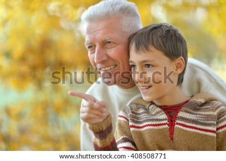 Grandfather and grandson in park - stock photo