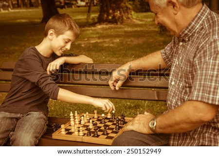 Grandfather and grandson in the park - stock photo