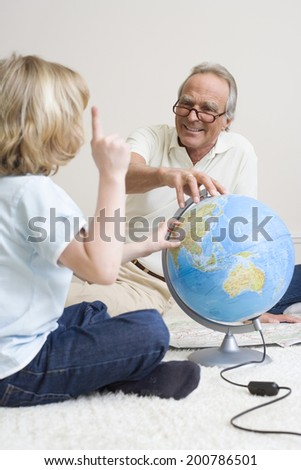 Grandfather and grandson looking at globe - stock photo