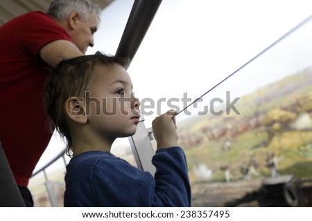 Grandfather and grandson looking at picture in museum - stock photo