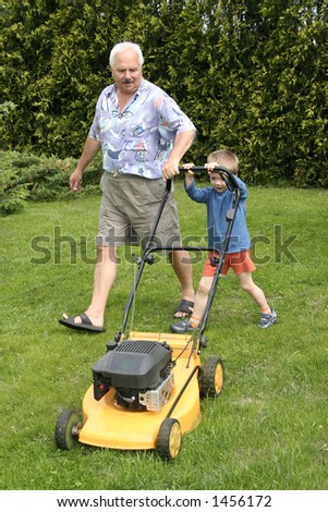 Grandfather and grandson mowing grass