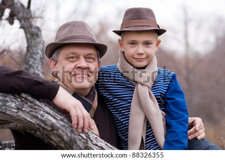 Grandfather and grandson outdoors. Autumn. A tree. - stock photo