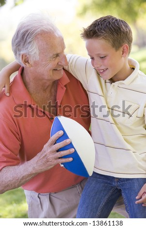 Grandfather and grandson outdoors with football smiling - stock photo