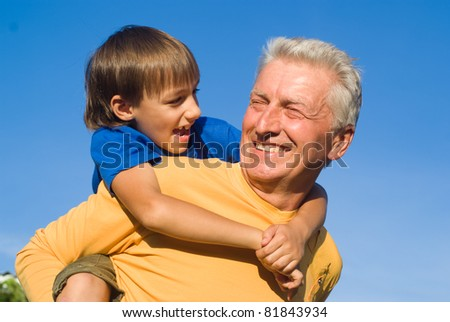 grandfather and grandson playing at the nature - stock photo