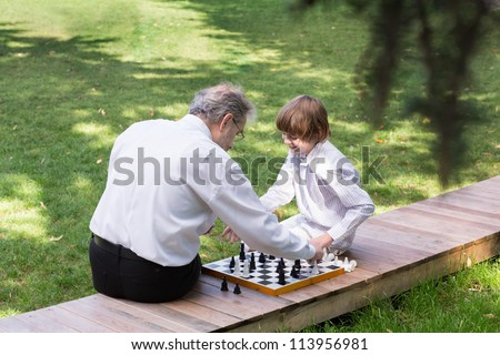 Grandfather and grandson playing chess in a park - stock photo