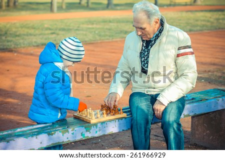 Grandfather and grandson playing chess on a bench outdoors - stock photo