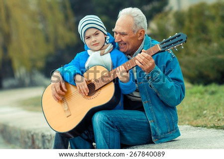 Grandfather and grandson playing guitar outdoors - stock photo