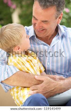 Grandfather And Grandson Relaxing On Sofa Together - stock photo